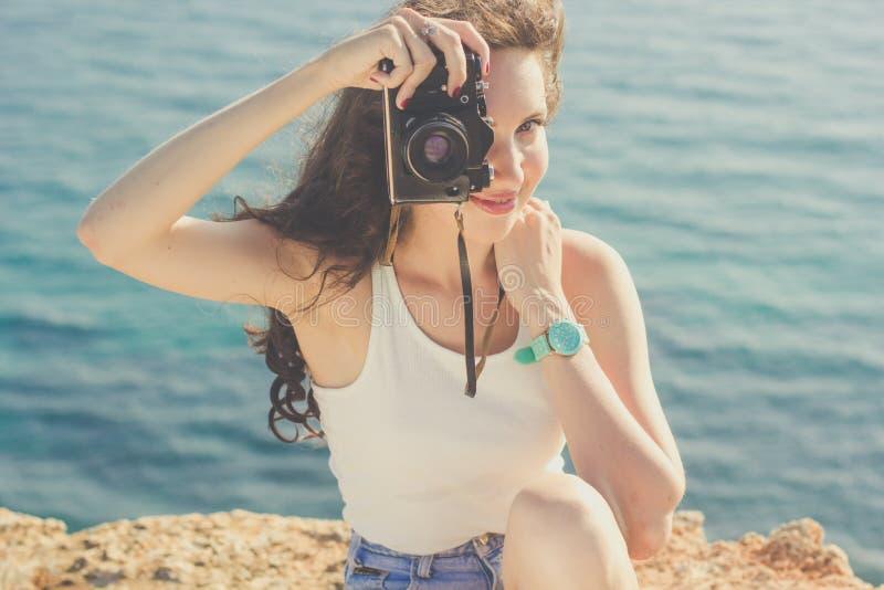 Κορίτσι τουριστών που κάνει τις εικόνες από την παλαιά κάμερα στην κορυφή βουνών στοκ εικόνα