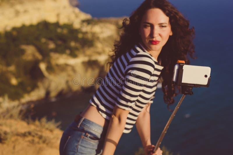 Κορίτσι τουριστών που κάνει selfie τη φωτογραφία με το ραβδί στην κορυφή βουνών στοκ εικόνες