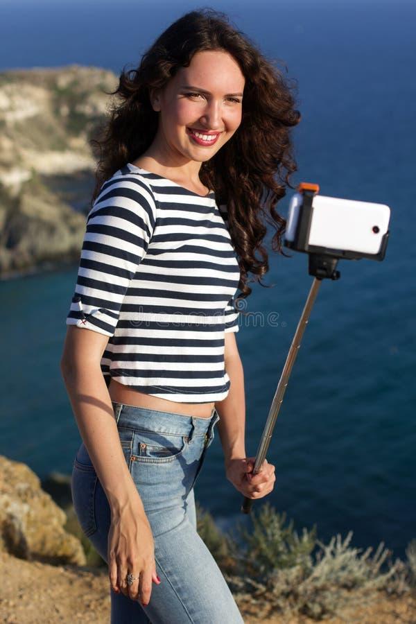 Κορίτσι τουριστών που κάνει selfie τη φωτογραφία με το ραβδί στην κορυφή βουνών στοκ φωτογραφίες