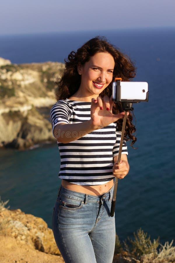 Κορίτσι τουριστών που κάνει selfie τη φωτογραφία με το ραβδί στην κορυφή βουνών στοκ φωτογραφία
