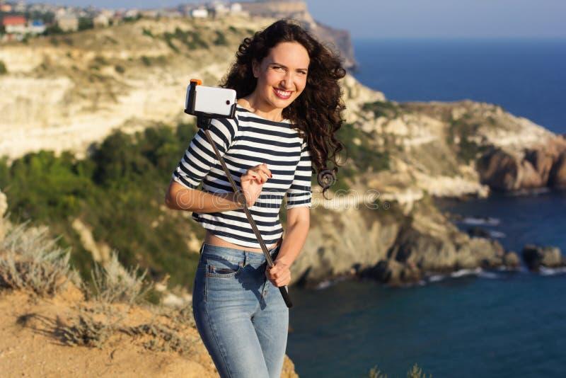 Κορίτσι τουριστών που κάνει selfie τη φωτογραφία με το ραβδί στην κορυφή βουνών στοκ εικόνες με δικαίωμα ελεύθερης χρήσης