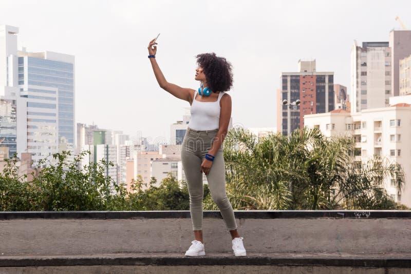 Κορίτσι τουριστών σπουδαστών hipster που χρησιμοποιεί το κινητό τηλέφωνό της στο photograp στοκ εικόνες