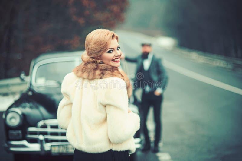 Κορίτσι φωτογραφιών, ένα άτομο και ένα αναδρομικό αυτοκίνητο στοκ φωτογραφίες