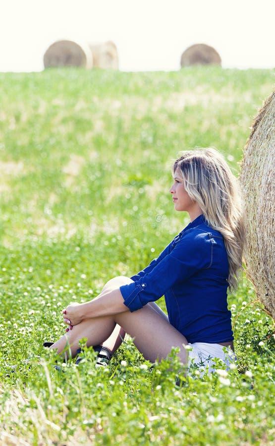 Κορίτσι χώρας κοντά σε μια θυμωνιά χόρτου πράσινος χορτοτάπητας στοκ εικόνες