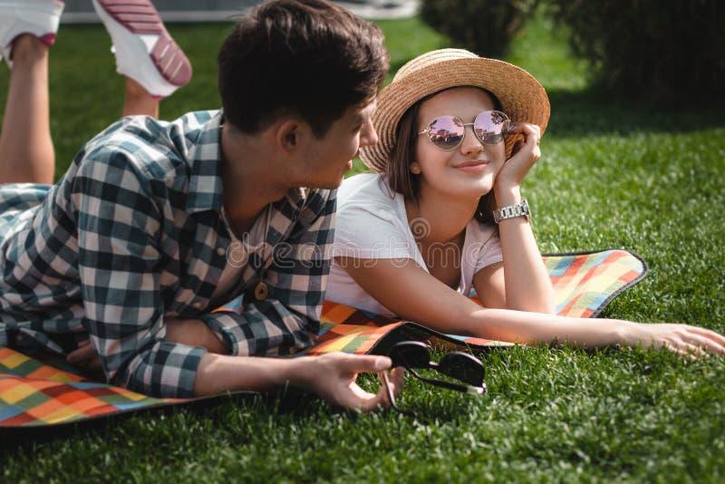 Κορίτσι ANG αγοριών Teens που βάζει στο κάλυμμα στο πάρκο στοκ φωτογραφία