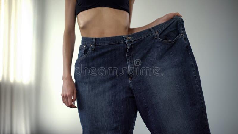 Κορίτσι Anorexic που φορά ένα παντελόνι-πόδι, παχιοί άνθρωποι εναντίον της μεμβρανοειδούς, γρήγορης απώλειας βάρους στοκ εικόνα