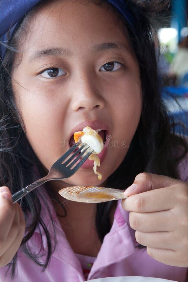 Κορίτσι Asain που τρώει τη σχάρα κοχυλιών θάλασσας με το δίκρανο στοκ φωτογραφία με δικαίωμα ελεύθερης χρήσης
