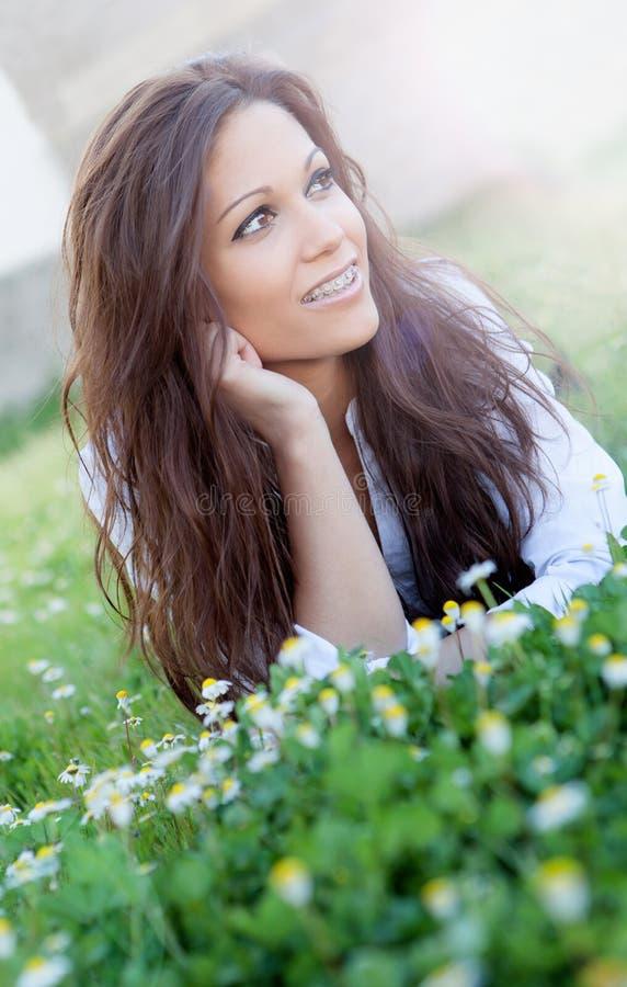 Κορίτσι Brunette με τα υποστηρίγματα που βρίσκονται στη χλόη με πολλά λουλούδια στοκ εικόνα