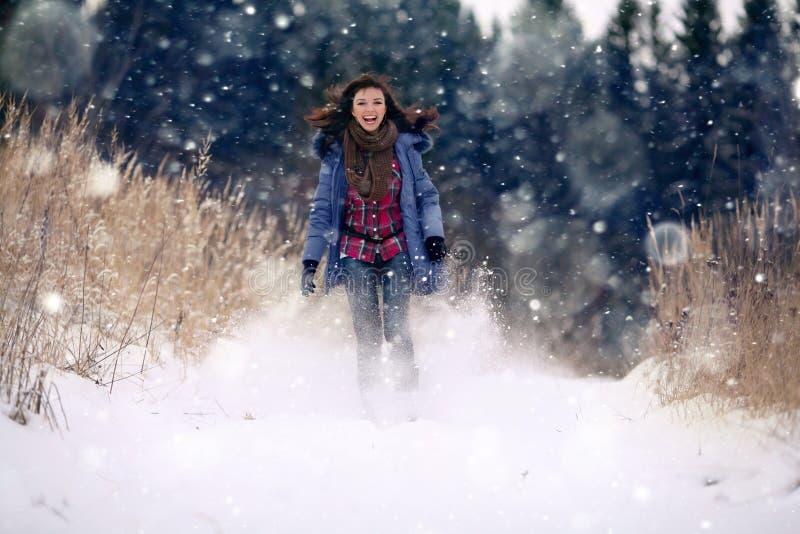 κορίτσι brunette που τρέχει στο χιονώδες δάσος στοκ φωτογραφία με δικαίωμα ελεύθερης χρήσης
