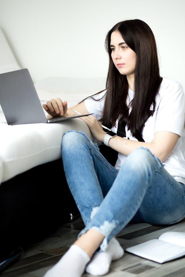 Κορίτσι Brunette που χρησιμοποιεί το lap-top και το smartphone στο άνετο εγχώριο εσωτερικό Έννοια τεχνολογίας και επικοινωνίας στοκ εικόνες