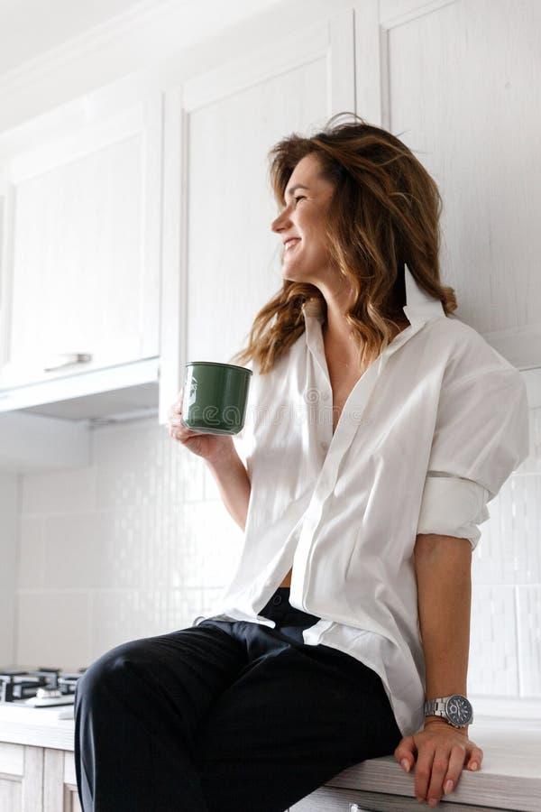 Κορίτσι Brunette στο άσπρο πουκάμισο στην κουζίνα στοκ εικόνα