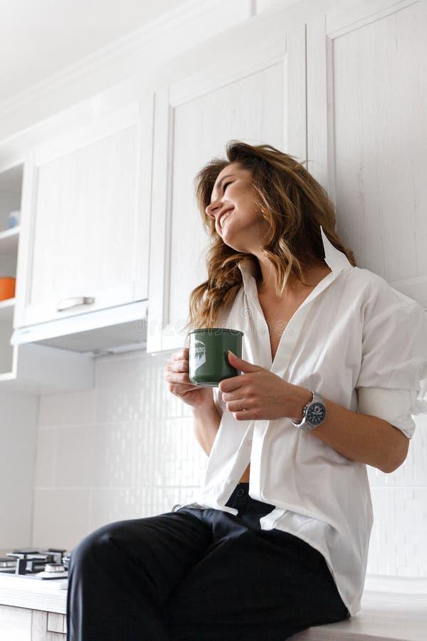 Κορίτσι Brunette στο άσπρο πουκάμισο στην κουζίνα στοκ φωτογραφία
