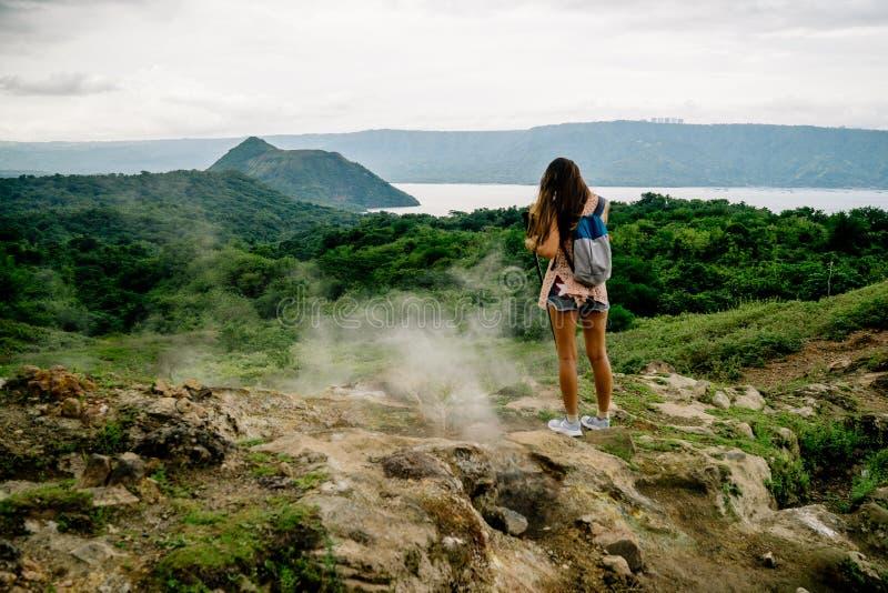 κορίτσι filipina που εξετάζει τη taal λίμνη κρατήρων ηφαιστείων από το ίχνος κατά μήκος του πλαισίου κοντά στη Μανίλα στις Φιλιππ στοκ φωτογραφίες