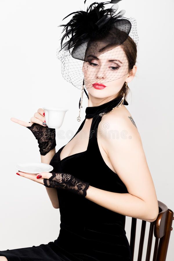Κορίτσι Glamor με ένα φλιτζάνι του καφέ η γυναίκα μόδας πίνει coffe ή καυτό τσάι στοκ φωτογραφία