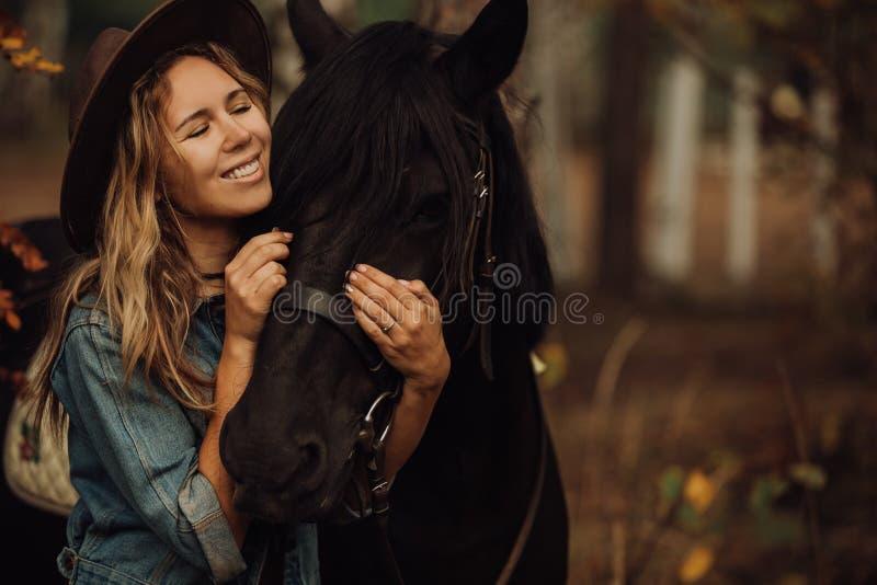 Κορίτσι Hipster με ένα άλογο στο χαμόγελο ξύλων στοκ εικόνα