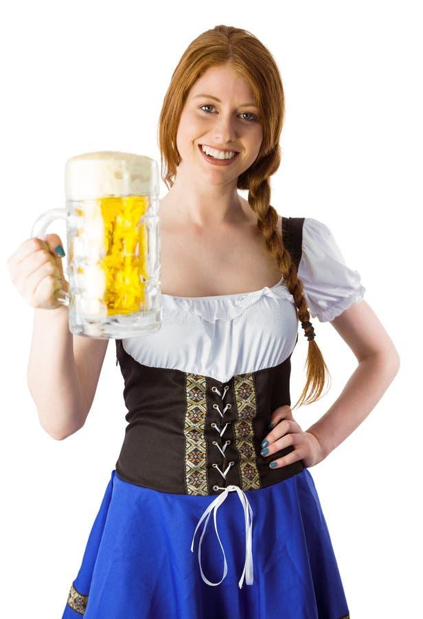 Κορίτσι Oktoberfest που χαμογελά στην μπύρα εκμετάλλευσης καμερών στοκ εικόνα με δικαίωμα ελεύθερης χρήσης