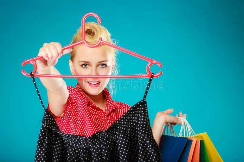 Κορίτσι Pinup με τις τσάντες αγορών που αγοράζει τη φούστα Πώληση στοκ εικόνες