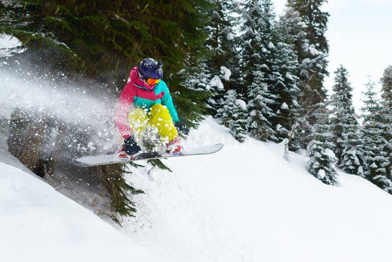 Κορίτσι snowboarder που πηδά στο δάσος που φεύγει πίσω από τον ψεκασμό του s στοκ εικόνα με δικαίωμα ελεύθερης χρήσης