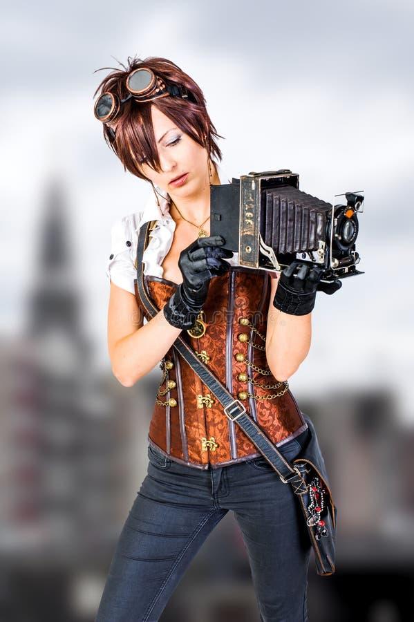 Κορίτσι Steampunk στον εκλεκτής ποιότητας κορσέ με την αναδρομική κάμερα στοκ φωτογραφία