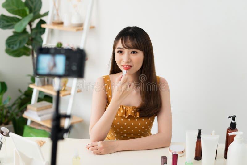 Κορίτσι videoblogger ή βίντεο αρχείων ομορφιάς blogger για τους συνδρομητές Παρουσιάζει κραγιόν και λέει πώς να το χρησιμοποιήσει στοκ φωτογραφία