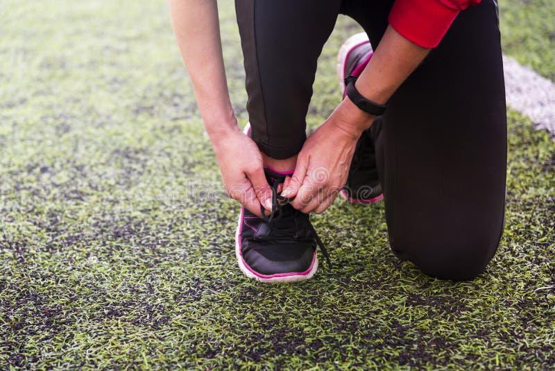 Κορδόνι δεσμών χεριών κοριτσιού στα αθλητικά παπούτσια στο αθλητικό στάδιο στοκ εικόνα