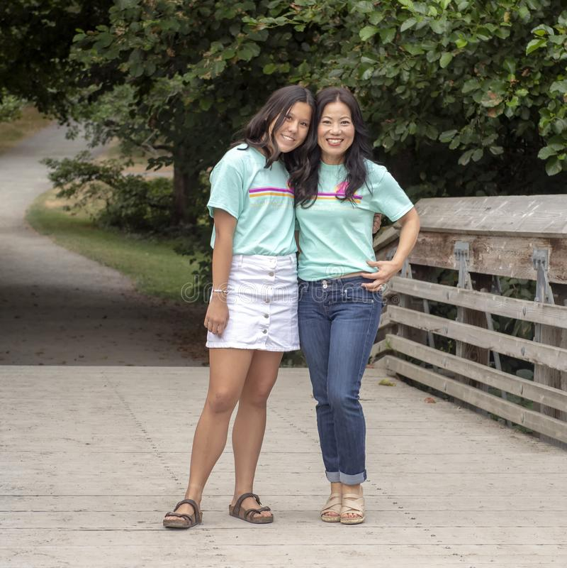 Κορεατική μητέρα με την τοποθέτηση έφηβη κόρη της σε μια ξύλινη γέφυρα στο δενδρολογικό κήπο πάρκων της Ουάσιγκτον, Σιάτλ, Ουάσιγ στοκ εικόνα με δικαίωμα ελεύθερης χρήσης