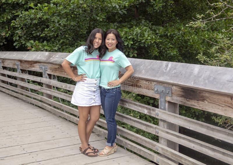 Κορεατική μητέρα με την τοποθέτηση έφηβη κόρη της σε μια ξύλινη γέφυρα στο δενδρολογικό κήπο πάρκων της Ουάσιγκτον, Σιάτλ, Ουάσιγ στοκ φωτογραφία
