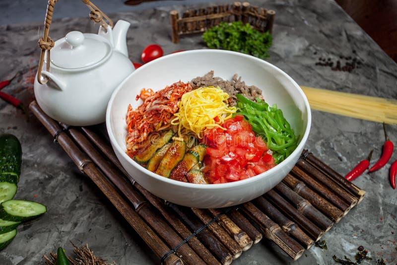 Κορεατικό νουντλς με το kimchi, ντομάτες, τσίλι στο άσπρο κύπελλο στο bamb στοκ φωτογραφίες με δικαίωμα ελεύθερης χρήσης