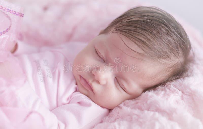 Κοριτσάκι κοιμισμένο στο ρόδινο κρεβάτι Νεογέννητος Ρόδινα ενδύματα στοκ εικόνες