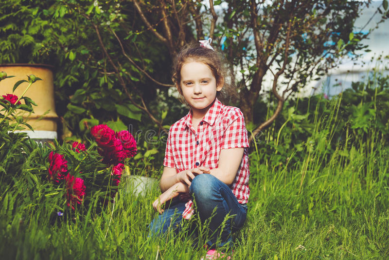 κοριτσάκι κοντά στον κλάδο peony στο θερινό κήπο στοκ φωτογραφία με δικαίωμα ελεύθερης χρήσης