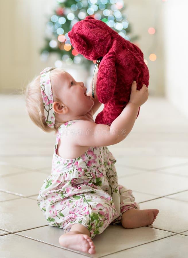Κοριτσάκι με τη teddy αρκούδα και το χριστουγεννιάτικο δέντρο στοκ εικόνες