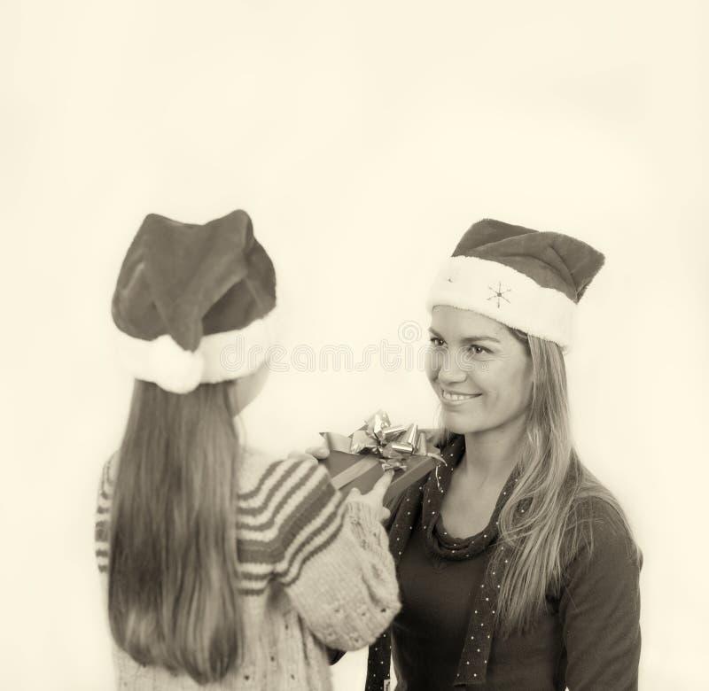 Κοριτσάκι που δίνει το δώρο Χριστουγέννων στην ευτυχή μητέρα της, που απομονώνεται επάνω στοκ φωτογραφία