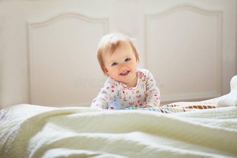 Κοριτσάκι που σέρνεται στο κρεβάτι και το γέλιο στοκ φωτογραφίες με δικαίωμα ελεύθερης χρήσης