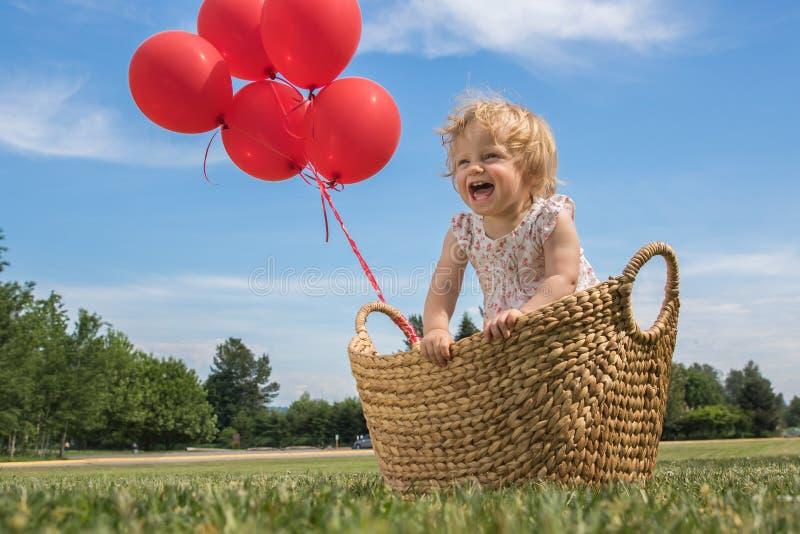 Κοριτσάκι σε ένα καλάθι με τα κόκκινα μπαλόνια στοκ φωτογραφίες με δικαίωμα ελεύθερης χρήσης