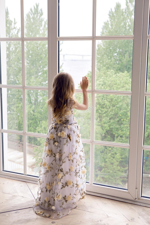 Κοριτσάκι στάσεις στις μακριές floral φορεμάτων στοκ εικόνα με δικαίωμα ελεύθερης χρήσης