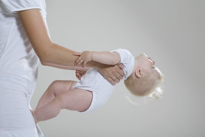 Κοριτσάκι στα χέρια της μητέρας στοκ εικόνα