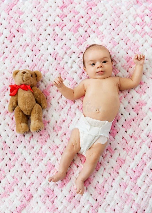 Κοριτσάκι στην πάνα που εναπόκειται σε teddy στο κάλυμμα στοκ φωτογραφίες με δικαίωμα ελεύθερης χρήσης