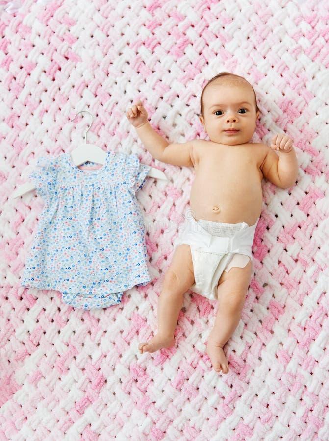 Κοριτσάκι στην πάνα που εναπόκειται στο φόρεμα στο κάλυμμα στοκ φωτογραφία
