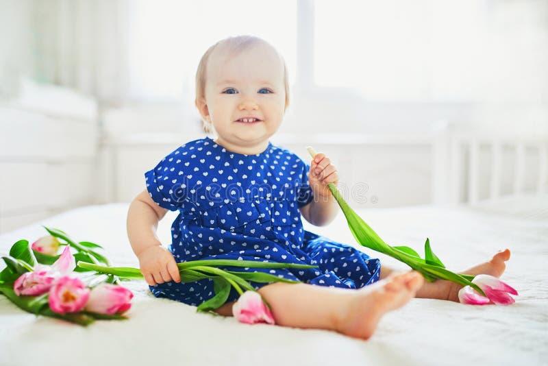 Κοριτσάκι στο μπλε παιχνίδι φορεμάτων με τη δέσμη των ρόδινων τουλιπών στοκ εικόνες