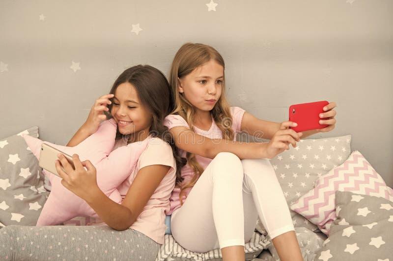 Κοριτσίστικο κόμμα πυτζαμών ελεύθερου χρόνου Μικρά bloggers smartphone κοριτσιών Σε απευθείας σύνδεση ψυχαγωγία Ερευνήστε το κοιν στοκ φωτογραφία