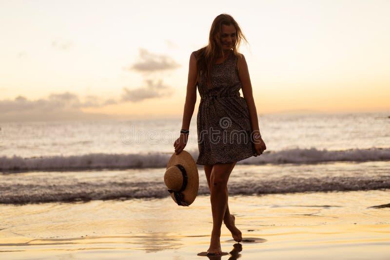 Κοριτσιού στο ηλιοβασίλεμα στην παραλία στοκ εικόνες