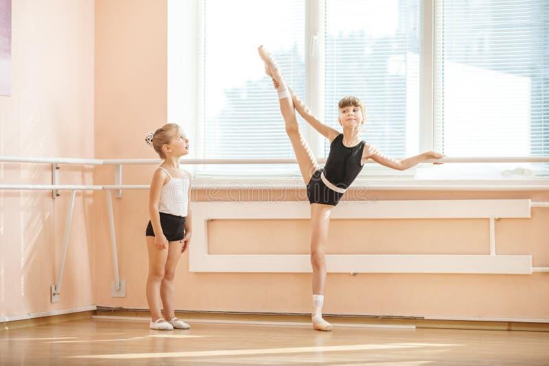 Κοριτσιών άσκηση σπουδαστών μπαλέτου προσοχής παλαιότερη στην μπάρα στοκ εικόνα με δικαίωμα ελεύθερης χρήσης
