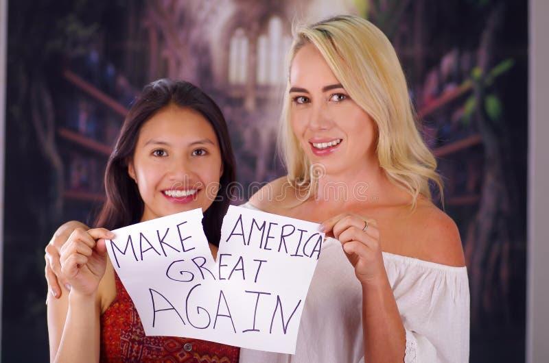 Κοριτσιών δύο χαμογελώντας και σπάζοντας ρατσισμού ιδιοσυγκρασία νέων γυναικών ξανθών και λατινικών από ένα αμερικανικό πρόσωπο κ στοκ εικόνα