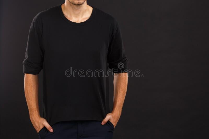 Κορμός ενός ευρωπαϊκού τύπου σε μια μαύρη μπλούζα Παραδίδει την τσέπη του παντελονιού Σε μια μαύρη ανασκόπηση indoors στοκ εικόνες