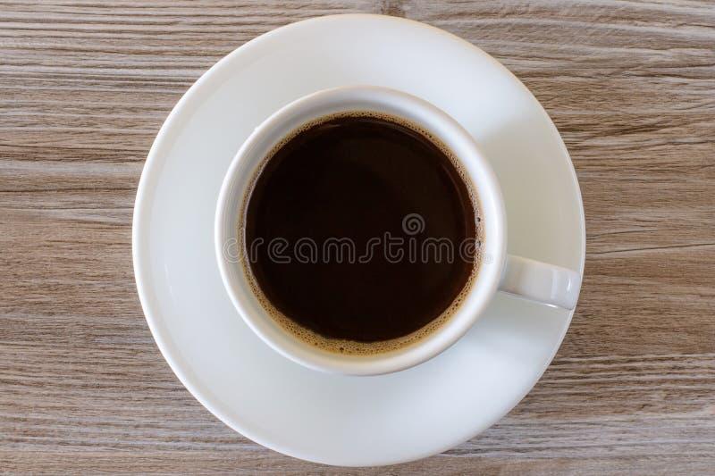 Κορυφή επάνω από την από πάνω στενή επάνω φωτογραφία άποψης του φλυτζανιού νόστιμου με το σκοτεινό φρέσκο καφέ πρωινού αφρού που  στοκ φωτογραφία με δικαίωμα ελεύθερης χρήσης