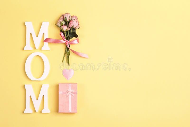 Κορυφή ημέρας μητέρων κάτω από τη σύνθεση του ξυπνητηριού, του δώρου και της ανθοδέσμης των τριαντάφυλλων στο κίτρινο υπόβαθρο στοκ φωτογραφίες