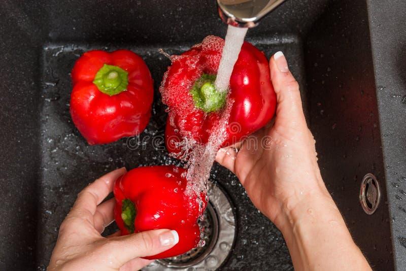 Κορυφή κάτω από την άποψη σχετικά με το μαύρο νεροχύτη με τα χέρια που πλένουν την κόκκινη πάπρικα κουδουνιών στοκ εικόνα
