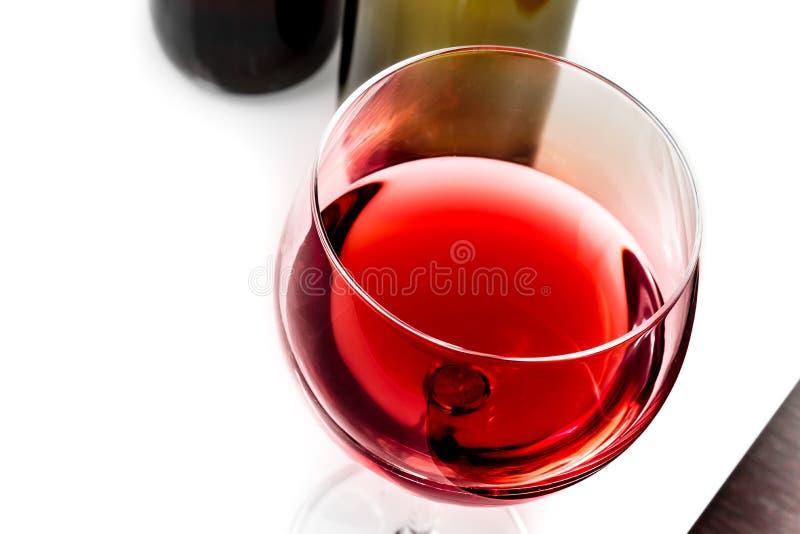 Κορυφή της άποψης του γυαλιού κόκκινου κρασιού κοντά στα μπουκάλια κρασιού στοκ εικόνα