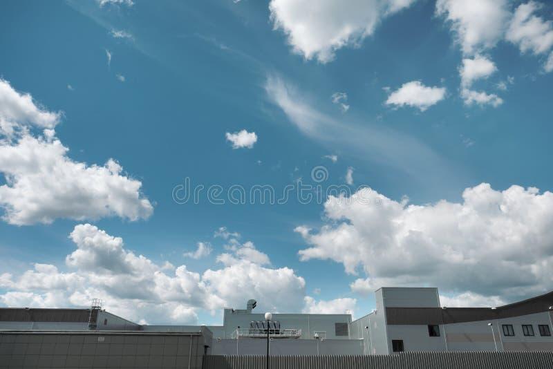 Κορυφή της οροφής ενός μεταλλικού κτιρίου παραγωγής πάνω από έναν γαλάζιο ουρανό με σύννεφα στοκ εικόνες με δικαίωμα ελεύθερης χρήσης