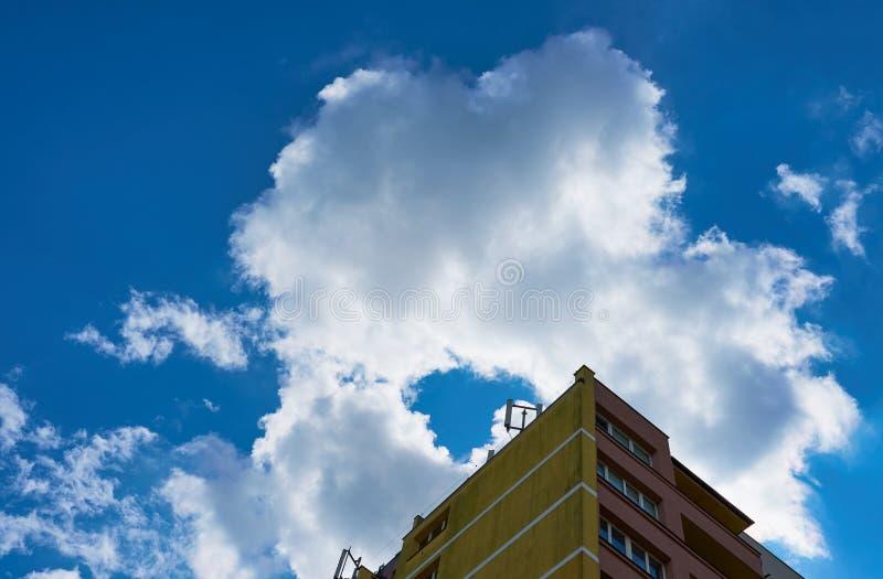 Κορυφή της πολυκατοικίας ενάντια σε έναν μπλε νεφελώδη ουρανό στοκ εικόνα